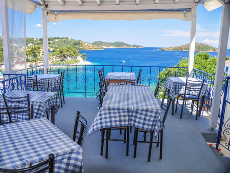 skiathos: A Harbour restaurant on Skopelos island with boats and island in the Aegean blue sea
