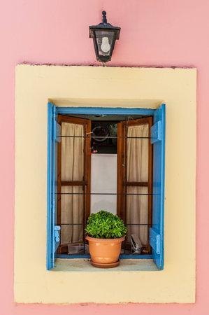 greek pot: Una finestra con le persiane blu, pallido circondano giallo e rosa e una pentola