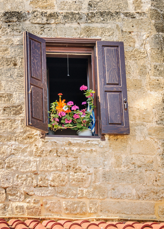 greek pot: A window with brown shutters, sand colour stone wall surrounding and pots of flowers