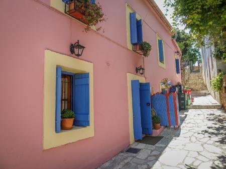 greek pot: Steet con le finestre e persiane blu, pallido rosa circondano e piante poted