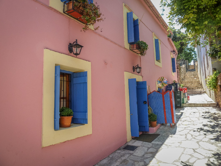 skiathos: Steet with windows and blue shutters, pale pink surround and poted plants