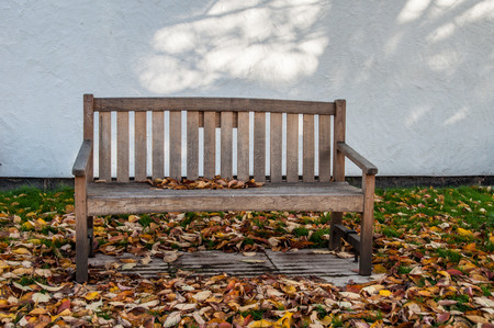 comfortable chair: Bench surrounded by autumn leaves, with a cream coloured background, in Essex, UK, churchyard Stock Photo