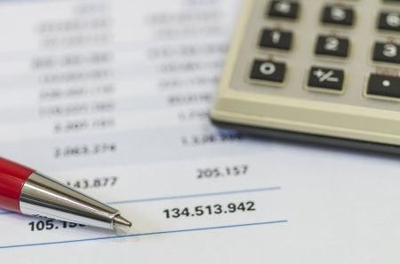 Accounting document with a calculator and pen photo