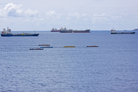 gig harbor: Cargo Ships provide a backdrop for the Falmouth Gig Club regatta in Cornwall, England on June 11, 2011