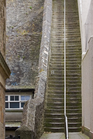 daunting: Long steep stone stairwell Stock Photo