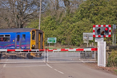 Passenger train on the level crossing near Eggesford station in Devon, England on March 24, 2012