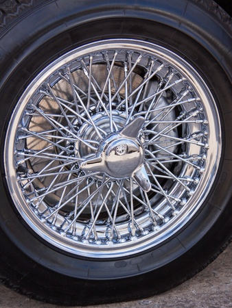 hubcap: The contrasting black rubber and polished metal of a vintage car tyre Stock Photo