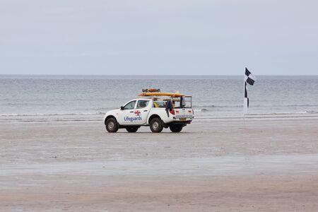 Westward Ho, England � May 28, 2012 - Lifeguard patrol on the beach next to a safe surfing flag at Westward Ho
