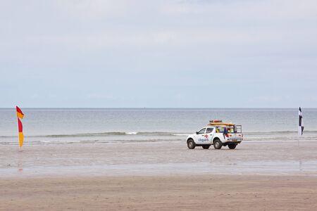 Westward Ho, England – May 28, 2012 - Lifeguard patrol on the beach between safety flags at Westward Ho