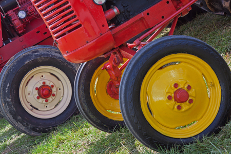 Bright wheels of restored vintage tractors at a farming show