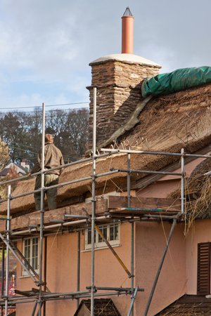 thatcher: Exford, Somerset UK - October 14, 2014 : Thatcher at work recovering an old cottage roof Editorial