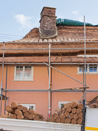 thatcher: Work in progress replacing roof thatch on a house on Exmoor in Somerset, England