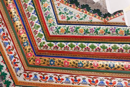 architecture design: Colorful detail from cornices beneath a ceiling in the City Palace at Udaipur India