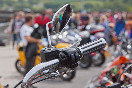 accelerator: One of the wing mirrors and hand controls of a parked motorcycle at a bike rally UK Stock Photo