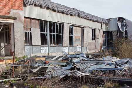 smithereens: Debris and scrap metal stacked outside a derelict industrial site Stock Photo