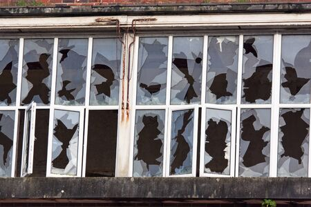 economic depression: Array of smashed factory windows Stock Photo