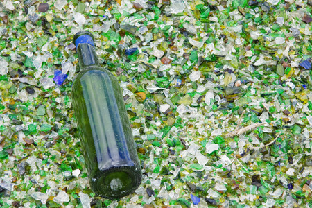 Discarded bottle lying on glass particles at a recycling centre