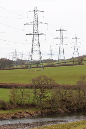 torres el�ctricas: Las torres de electricidad que dominan las tierras agr�colas Foto de archivo