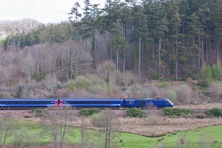 speeding: Passenger train speeding through English countryside Stock Photo