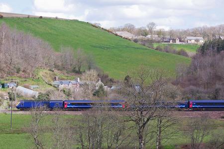 long haul journey: Passenger train passing through Devon farmland