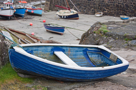 Small blue boat at the head of a harbour at low tide Stock Photo