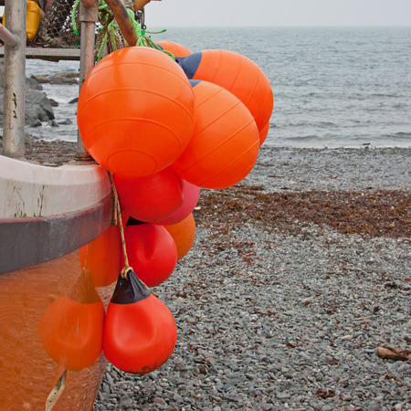 beached: Colorful floats on a beached fishing vessel