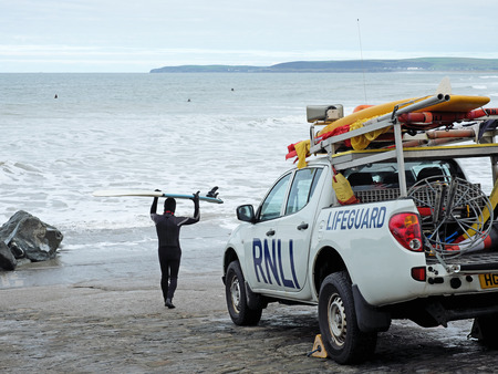 perilous: WESTWARD HO!, ENGLAND SEPTEMBER 20, 2016: A surfer heads towards the water past a vehicle belonging to the Royal National Lifeboat Institution, a 190 years old charity protecting 180 British beaches Editorial