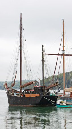 A ketch, a traditional wooden sailing vessel, moored on the Fal river in Cornwall, England Stock Photo