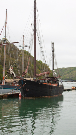 Traditional wooden sailing vessel moored in a Cornish river