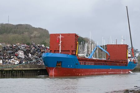Cargo boat being loaded with crushed metal from scrapped cars at a UK port