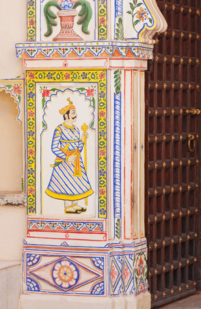 UDAIPUR, INDIA – MARCH 5, 2015: Decoration adorning a gateway to the City Palace characteristic of traditional Rajasthani wall painting Stock Photo - 84098955