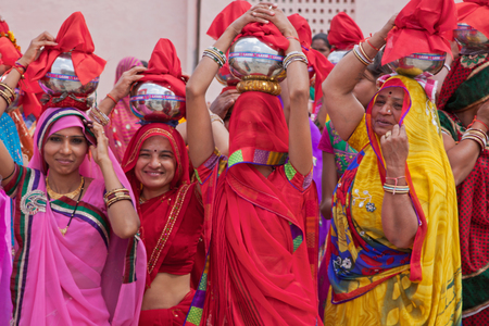 RAJSAMAND, INDIA – MARCH 7, 2015: Women in typically colorful dress at the start of a procession during the Hindu festival of Gangaur which lasts for 16 days and is marked throughout the state of Rajasthan to celebrate marital fidelity and the onset of  Editorial