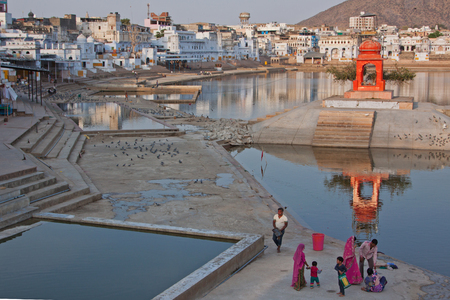 hallowed: PUSHKAR, INDIA – MARCH 12, 2015: Unidentified family in the early evening at  a place of pilgrimage for devout Hindus. The lake is deemed holy as it is believed to have sprung from a lotus flower dropped by the god Brahma