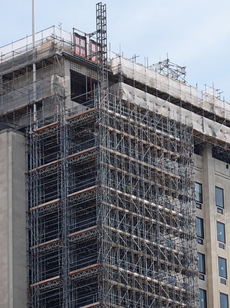 Extensive scaffolding provides access for work in progress on a tower block in UK