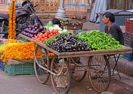 Ahmedabad, India – October 29, 2016: Fruit and vegetable seller in front of a temple gateway in the Kalupur district of the old city