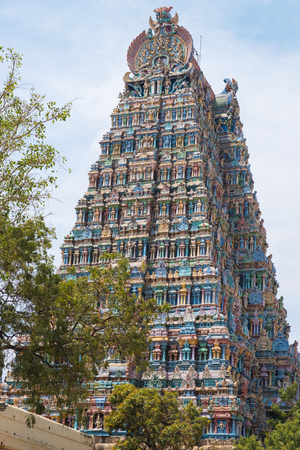 The western Gopuram, or gateway, to the Meenakshi Hindu temple complex  covering 45 acres in the heart of Madurai in Tamil Nadu, India. The 4 main entrances have the tallest towers of the 14 pyramidial towers on the sacred site Фото со стока