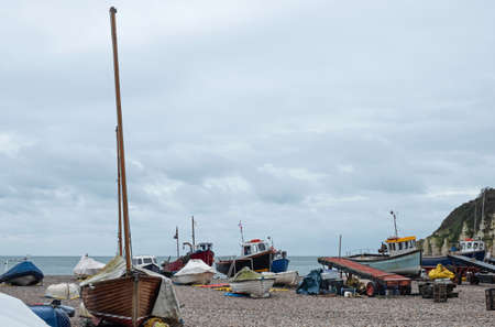 Boats of the local fishing fleet stranded on the pebble beach at Beer in south east Devon, UK. Vessels are towed to and from the sea by tractor