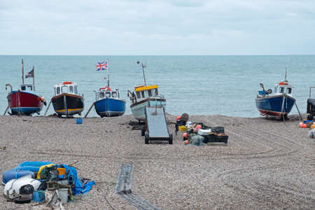 Some of the local fishing fleet stranded on the pebble beach at Beer in south east Devon, UK. Vessels are towed to and from the sea by tractor