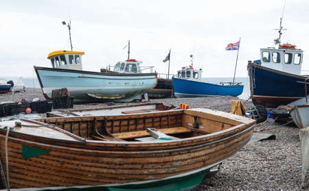 Fishing boats stranded on the pebble beach at Beer in south east Devon. Vessels are towed to and from the sea by tractor Imagens