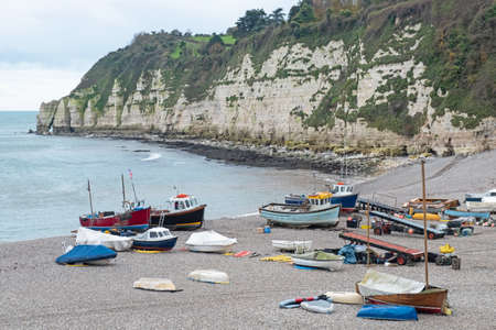 The local fishing fleet stranded on the pebble beach at Beer in south east Devon, UK. Vessels are towed to and from the sea by tractor