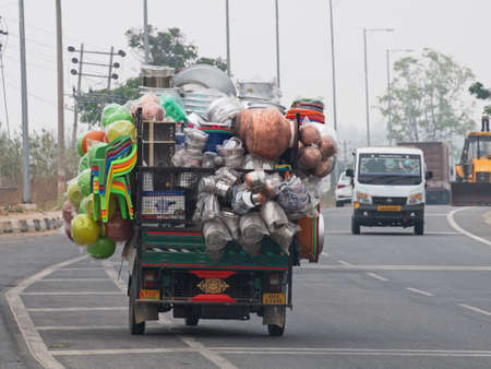 Overloaded commercial vehicle carrying household goods on a main highway south of Mysore. Excessive loads are commonplace on Indian roads Banque d'images