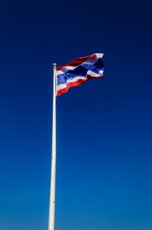 Flag of Thailand with flag pole waving in the wind blue sky photo