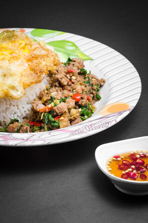 Rice topped with stir-fried pork and basil with fried egg photo