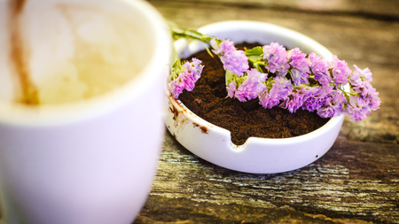 Beautiful flower and coffee ground on vintage wooden background, selective focus photo