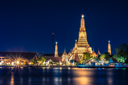 Night time view of Wat Arun Temple across Chao Phraya River in Bangkok, Thailand