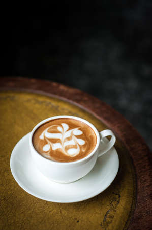 A cup of coffee with flower pattern in a white cup on vintage leather background photo