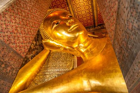 Reclining Buddha gold statue face. Wat Pho, Bangkok, Thailand photo