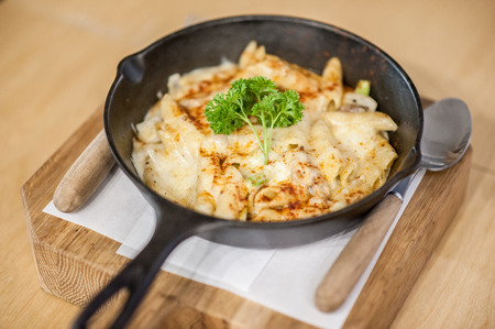 cheesy: Cheesy baked macaroni and cheese pasta portion with parmesan sprinkled on top - soft focus point Stock Photo