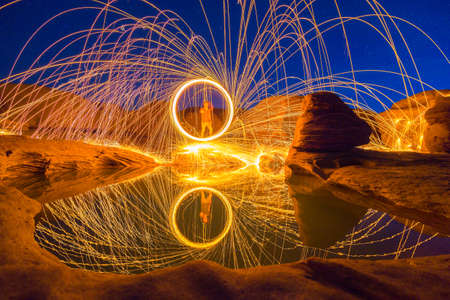 spins: Local man spins a fire for photography in mekong river (Sam Pan Bok grand canyon) ubon ratchathani province asia thai