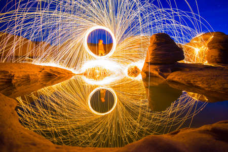 Local man spins a fire for photography in mekong river (Sam Pan Bok grand canyon) ubon ratchathani province asia thai